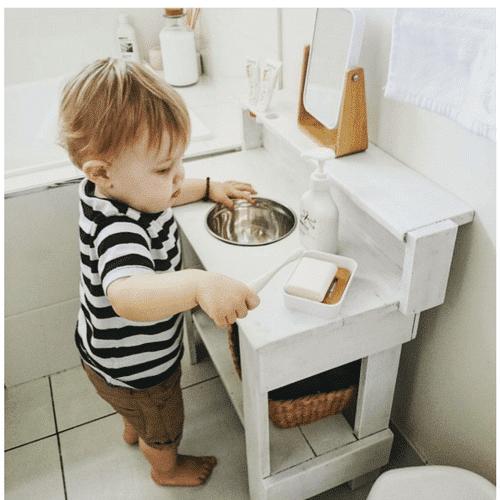 un enfant qui fait sa toilette par lui même, inspiration Montessori