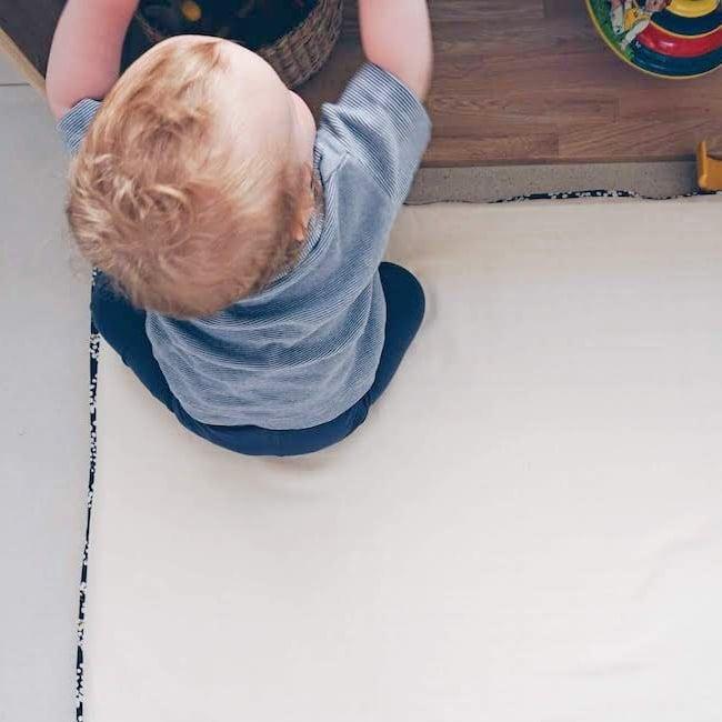 Enfant entre 16 et 24 mois qui attrape un objet dans une étagère Montessori