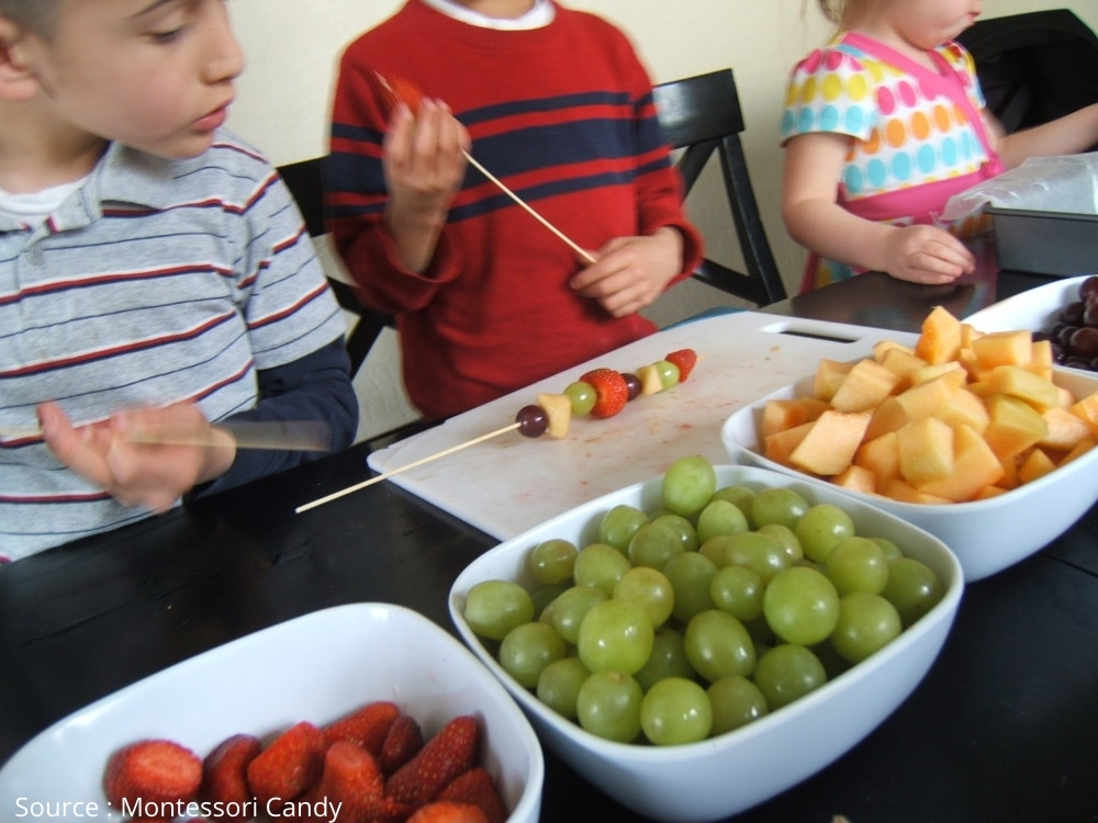 activité Montessori montrant enfants qui préparent de brochettes de fruits