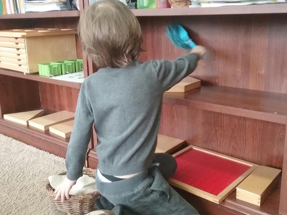enfant qui dépoussière un meuble Montessori